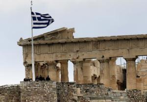 Tourists stand near the temple of Parthenon atop the ancient site of the Athens Acropolis on a cold and windy day